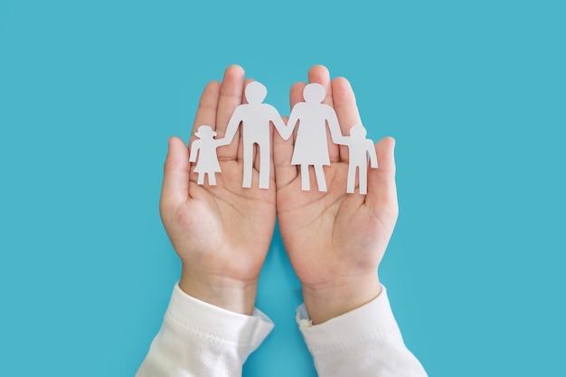子供の手は青い背景に家族の白いシルエットを保持しています。愛と幸福の概念。
