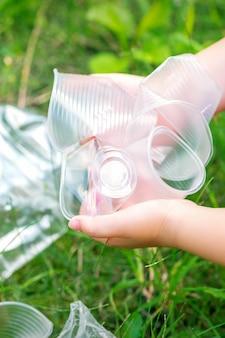 子供の手が草の中の使用済みプラスチック器具から公園をきれいにします