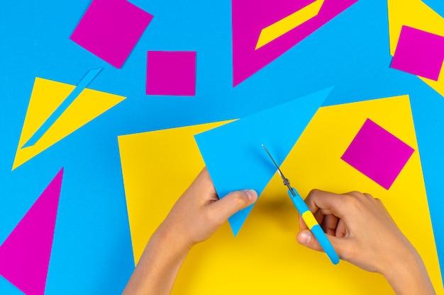 子供の手がテーブルでハサミで色紙を切る