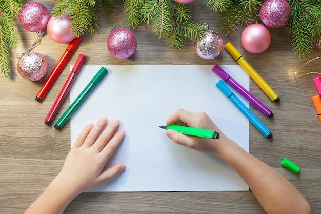 아이의 손에 종이에 마커가있는 크리스마스 트리를 그립니다.