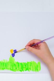 白い紙に花を描く子供の手。上面図。子供とアースデイのコンセプト。