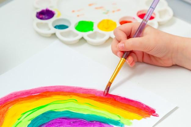 虹を描く子供の手。