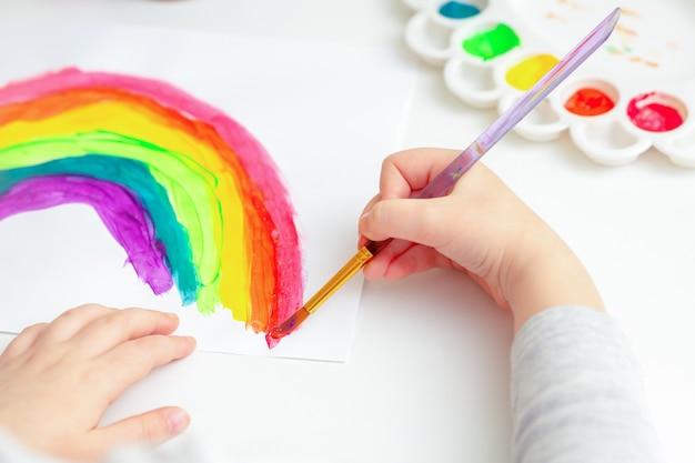 Детские руки, рисующие радугу