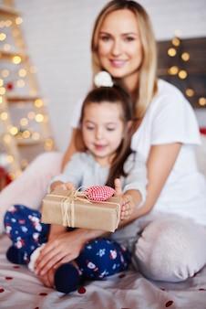 Mani del bambino che danno i regali di natale
