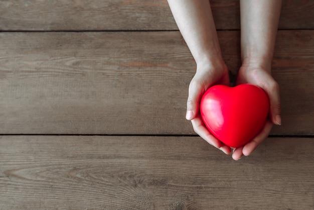 子供の手は木のシーンに小さな赤いハートを持っています、子供のクローズアップはサインの形で臓器を与えます