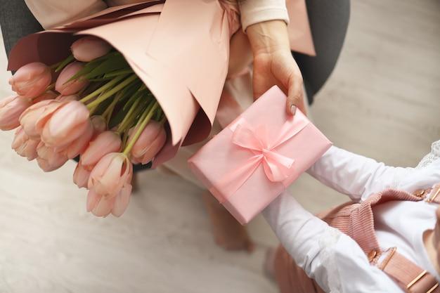Руки ребенка держат красивую розовую подарочную коробку с лентой и розовым цветком тюльпана. вид сверху, крупный план. готовимся к праздникам.