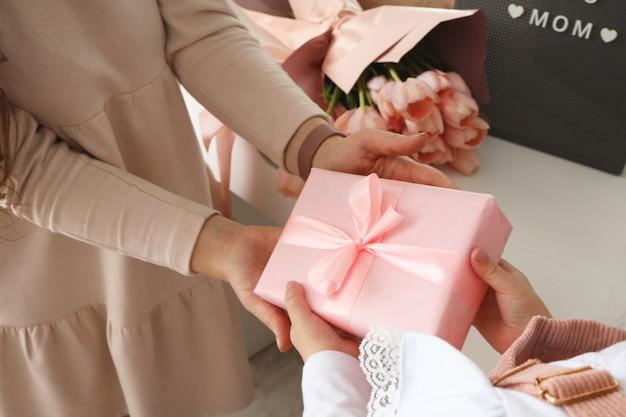 Руки ребенка держат красивую розовую подарочную коробку с лентой. розовый цветок тюльпана и знак, я люблю тебя, мама в фоновом режиме. вид сверху, крупный план. готовимся к праздникам.