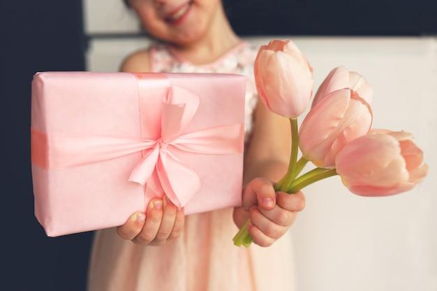 Руки ребенка держат красивую розовую подарочную коробку с лентой. розовый цветок тюльпана. крупным планом. готовимся к праздникам.