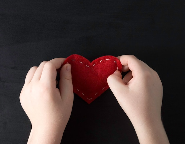 The child's hands hold a red cloth heart on a black background. concept of love, baby love