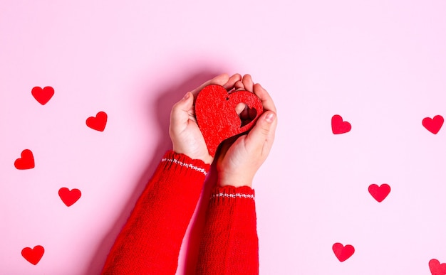 Child's hands hold a wooden red heart on pink