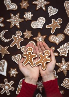 自家製ジンジャーブレッドマンクッキーを持っている子供の手。上面図