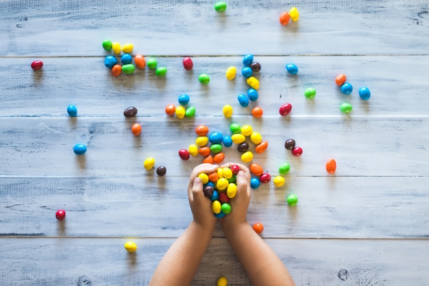 A child's hands holding pile of colorful candies