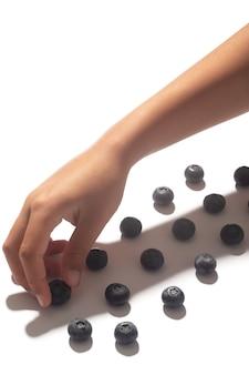 子供の手は影と白い背景で隔離の列にブルーベリーを配置します