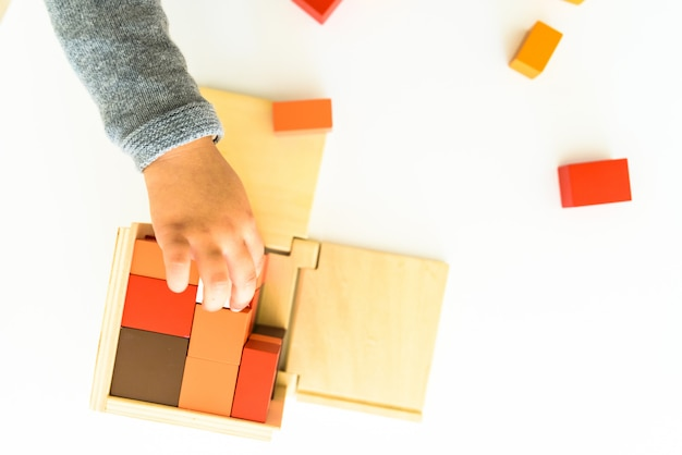 Руки ребенка учатся приспосабливать части в деревянной головоломке 3d.