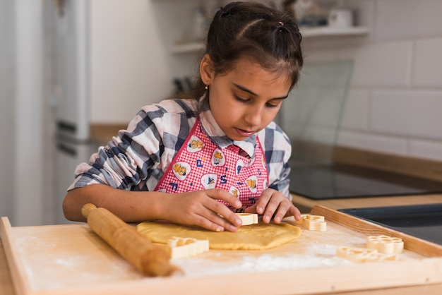 Руки ребенка делают печенье из сырого теста в форме сердца, крупным планом. ребенок готовит печенье и вырезает из раскатанного теста фигурки в виде сердца. крупный план.