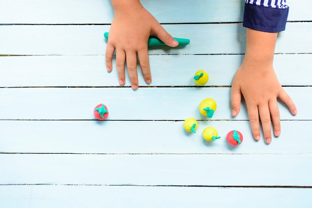 Child's hands molding clay and using creativity for making line and fruits