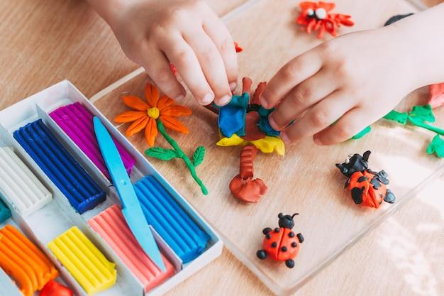 子供の手は柔らかい粘土からフィギュアを彫刻します。子供たちとの教育的で面白いクラス。閉じる。上面図