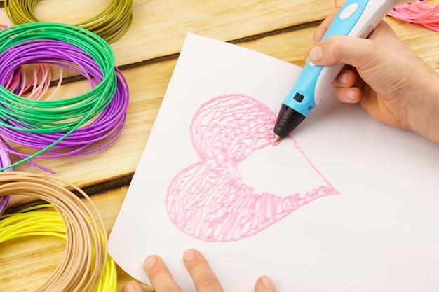 Руки ребенка с помощью ручки для 3d-печати. мальчик лепит сердечко на листе бумаги.