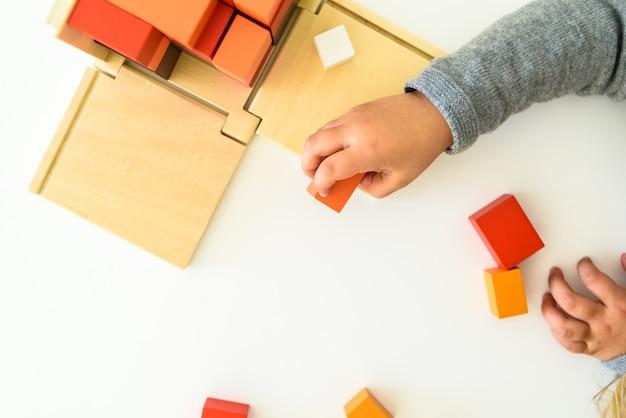Руки ребенка используют развивающую игрушку для их когнитивного развития.