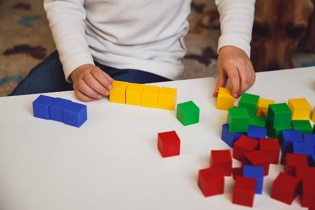 Руки ребенка с красочными кубиками на белой таблице. ребенок играет за столом. раннее развитие концепции ребенка.