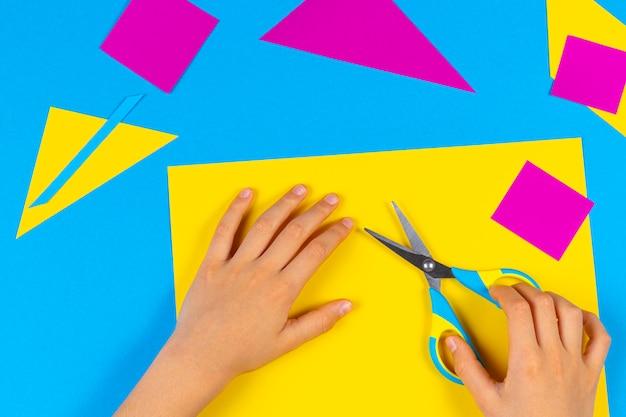 テーブルで色紙を切るハサミで子供の手