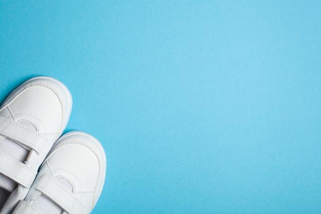밝은 파란색 파스텔 배경에 어린이의 새로운 흰색 스포츠 신발 또는 운동화. 텍스트 복사 공간
