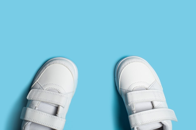 밝은 파란색 파스텔 배경에 어린이의 새로운 흰색 스포츠 신발 또는 운동화.