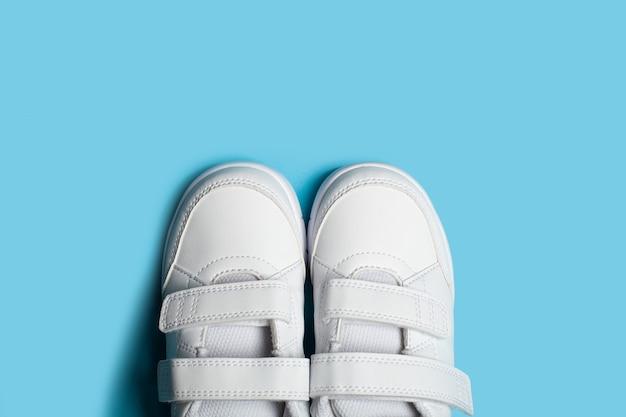 Новые детские белые спортивные туфли или кроссовки на светло-голубом пастельном фоне.