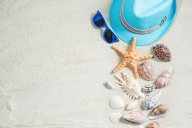Child`s stuff on the sea sand. shells, hat and sunglasses flat still. plane still of summer background