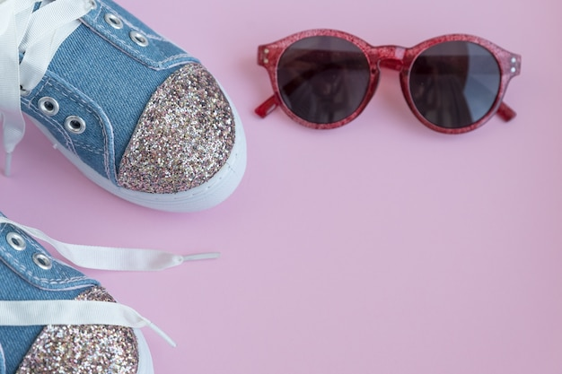 子供のテキスタイルレーススニーカー。ピンクの壁の女の子の靴。ファッションの子供の靴。スマートカジュアルでおしゃれなデニムと光沢のある靴。サングラスとトレンディなキッズスポーツシューズ。コピースペース。セレクティブフォーカス