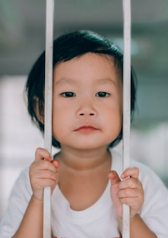 Child sadness eye behind steel door, asian child girl