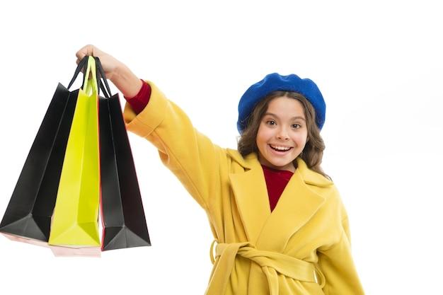 격리 된 흰색 배경 쇼핑에 만족 하는 아이. 쇼핑과 의류 쇼핑몰에 사로잡혀 있습니다. 쇼핑 중독 개념입니다. 당신이 쇼핑에 중독되었다는 신호. 꼬마 귀여운 소녀는 쇼핑백을 잔뜩 들고 있습니다.