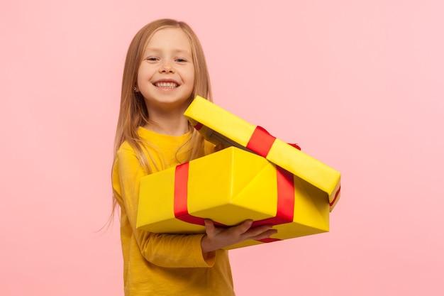 좋은 선물에 만족한 아이. 선물 상자를 열고 카메라를 향해 웃고 있는 매력적인 어린 소녀의 초상화, 생일, 크리스마스 휴일을 축하합니다. 분홍색 배경에 고립 된 스튜디오 촬영