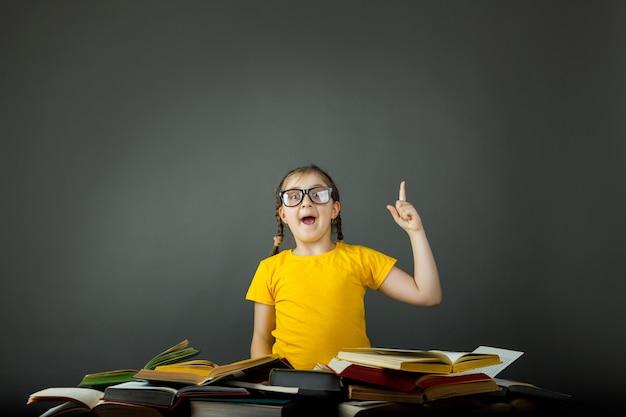 屋内の机、本の山で黒板を指している子供の学校の女の子