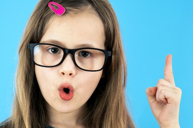 探している眼鏡をかけている子供の学校の女の子で私はアイデアのジェスチャーを持っています。