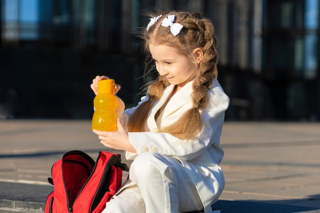 Child schoolgirl drink fresh water outdoors. little girl take out in schoolbag beverage between lessons on campus. back to school. kid healthy lifestyle.