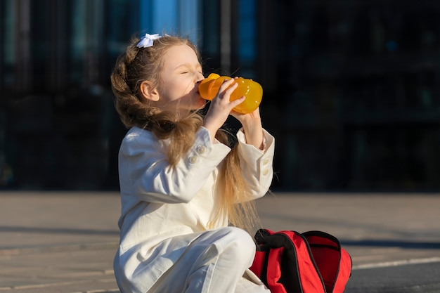 Child schoolgirl drink water outdoors. girl beverage. back to school. kid healthy lifestyle.