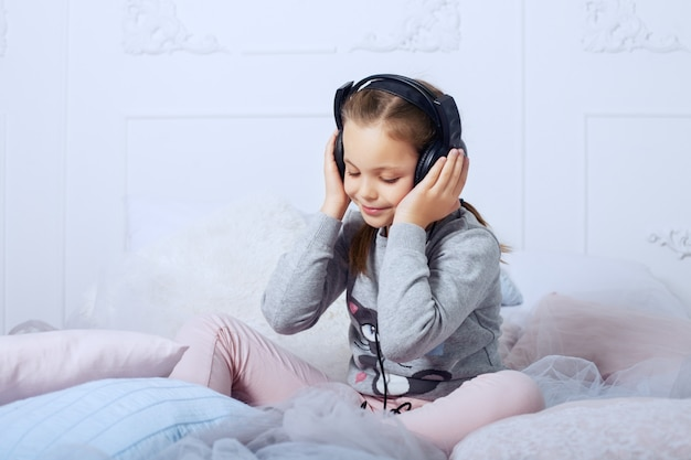 Child schoolgirl sitting on a bed and listening to an audiobook. childhood, education and music.