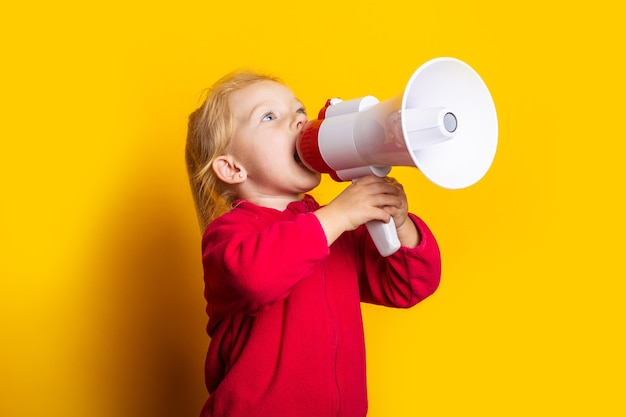 Child screaming megaphone looks up on bright yellow background.