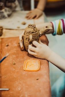 작은 찰흙 항아리를 조각하는 어린이