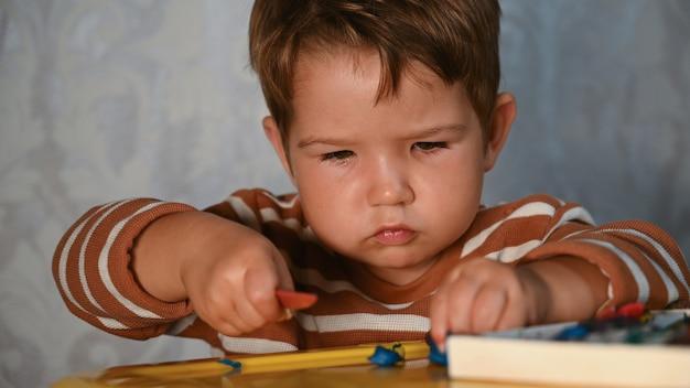 子供はテーブルで彫刻します。