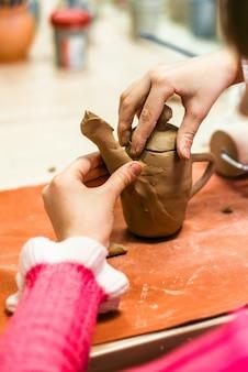어린이가 생 점토로 제품을 조각합니다.