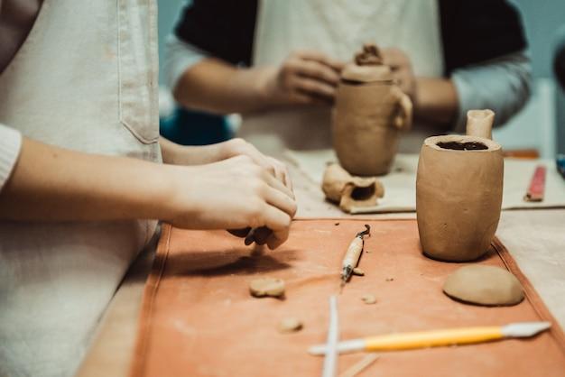 子供は生の粘土から製品を彫刻します