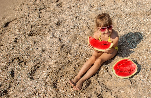 Child at sea eating a watermelon.
