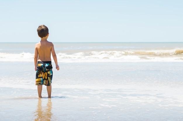 Child on seacoast in water