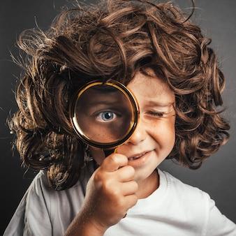 Ребенок видит через увеличительное стекло на черном