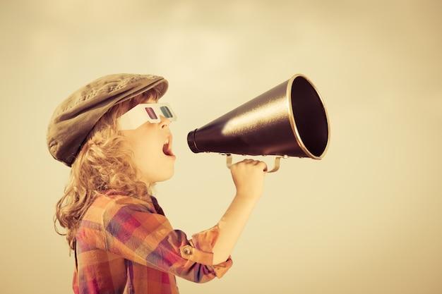 Ребенок кричит через старинный мегафон. концепция кино. ретро стиль