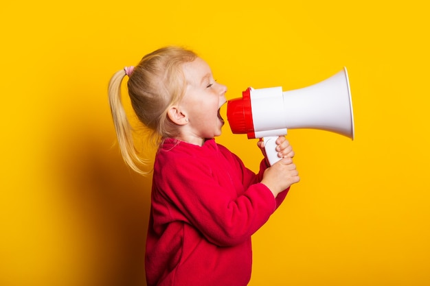 Child shouts into a white megaphone on a bright yellow background.
