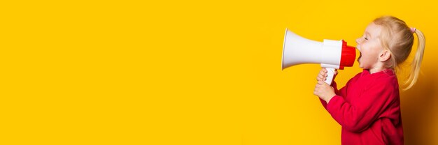 Child shouts into a white megaphone on a bright yellow background