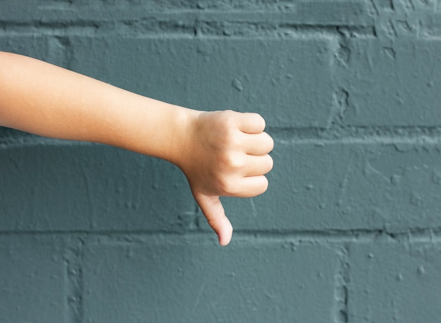 Child showing thumbs down on background of grey brick wall